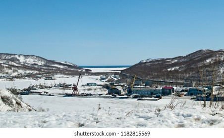A view of a frozen ice and snow-covered bay with ships and production buildings against the background of winter hills in Petropavlovsk-Kamchatsky