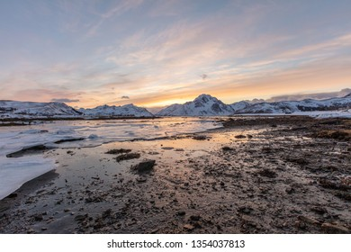 View of frozen lake on Lofoten islands in Norway with sunzet behind the snowy mountains