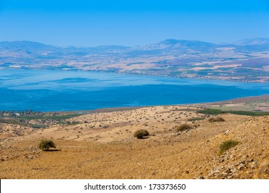View from Galilee Mountains to Galilee Sea, Kinneret, Israel. Golan Heights. Wonderful landscape with blue fog on the background and bright colors. Gradient from green to blue.