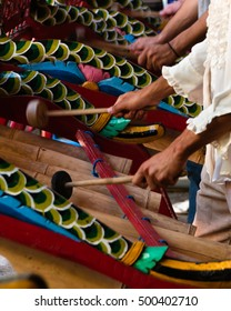 View of Gamelan musicians hands playing traditional instruments.