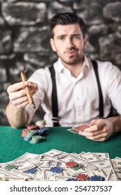 View of a gangster man is smoking a cuban cigar while he's playing poker.