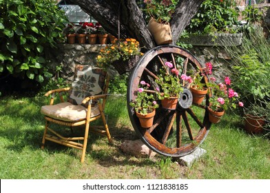 View of garden with hammock, wagon wheel and flowers, allegory of peace, of tranquility, of rest, of harmony, of calm, of freshness, of summer,