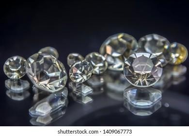View of gemstones, several diamonds with different sizes, dark background blur