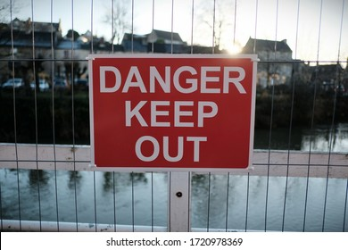 View of a Generic Sign Reading 'Danger Keep Out' Seen on a Metal Fence of a Derelict Riverside Building with the Setting Sun in the Background