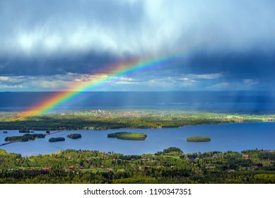 View from Gesundaberget mountain in Sweden with beautiful rainbow seen from above, Siljan lake visible in distance