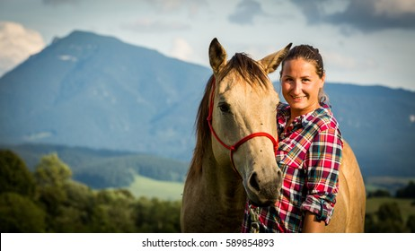 View of a girl with a blue and red mapped shirt with a horse in Slovakia