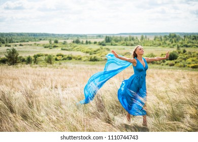 view of girl with flying blue material. outdoor shot. young adult woman wear long elegant dress. Dreaming female enjoy windy weather against green grass field, summer forest trees and sky