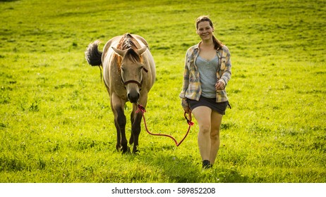 View of a girl with a horse on a field in Slovakian region Orava