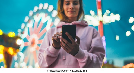 view girl pointing on screen smartphone on defocus background bokeh light in evening street attraction, woman using in hands mobile phone gadget in night city illumination online wifi internet concept