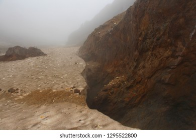 View of the glacier covered with volcanic ash and slag in the crater of the Mutnovsky volcano through the smoke from the fumarole field on the Kamchatka Peninsula, Russia.
