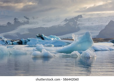 View of glaciers soming down from the mountains and icebergs floating in the glacier lagoon on a sunset, Jokulsarlon, South Iceland