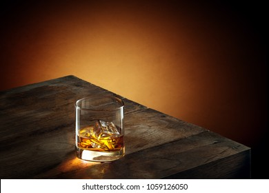 view of glas of  whiskey on wooden table on color background.