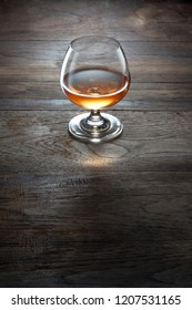 view of glass of  cognac on brown color wooden table surface