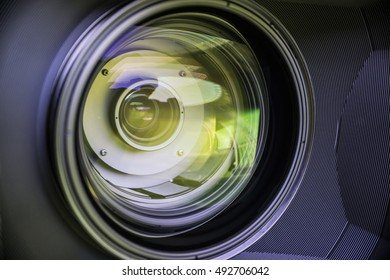 View of the glass elements in a camera lens. Objective under yellow light. Tilt-shift use.