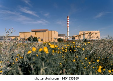 View of a glass factory in coexistence with nature. It is visible the chimney stack, the conveyor belt which brings the raw material into the plant. This factory is located in Bari.