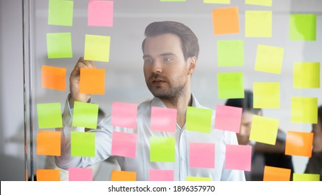View from glass wall concentrated skilled young caucasian IT manager writing notes or project steps on colored paper stickers, organizing workflow, checking tasks, optimizing processes in office.