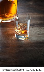 view of glass of  whiskey and a bottle aside on color background.