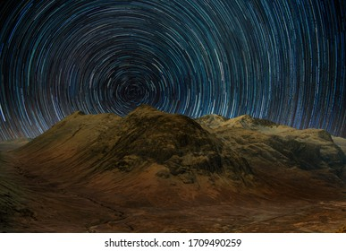 view of Glencoe mountains with star trail sky, highlands, Scotland, uk.