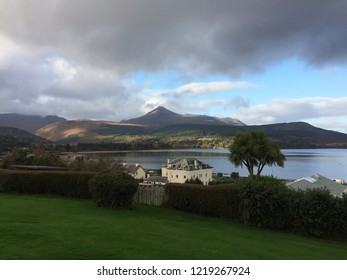 A view of Goat Fell from Brodick on the Isle of Arran with dark clouds in foreground and blue sky in background.