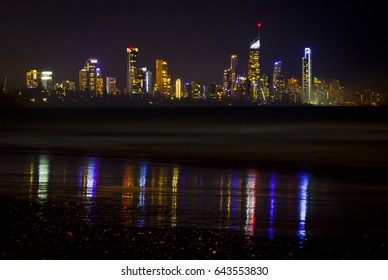 View of Gold Coast from Burleigh Heads. Night cityscape, lights reflected in the water.