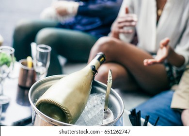 View of the golden champagne bottle in an ice bucket on the table in front of the seated people