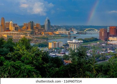 View of golden Cincinnati Ohio skyline from Covington Kentucky in summer with rainbow as rain storm departs during sunset.