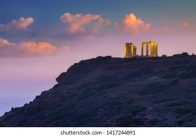 view to golden columns of greek temple on the cape under beautiful clouds in sunset time