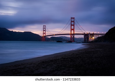 View of Golden Gate Bridge from Baker Beach at sunset in San Francisco, California.
