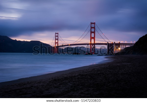 View of Golden Gate Bridge from Baker Beach at sunset in San Francisco, California.