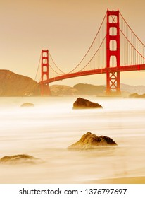 View of Golden Gate Bridge from Marshall's Beach in San Francisco at sunset.