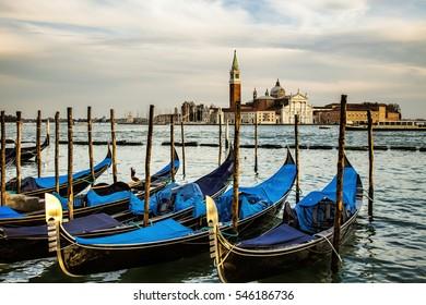View of gondolas and the Island of San Giorgi Maggiore from St. Mark's Square at dawn. In the back is the Church of San Giorgio Maggiore and the bell tower next on the Island of San Giorgio Maggiore.