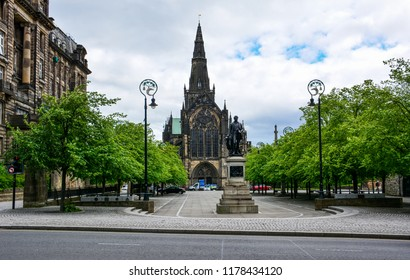 View of the gothic Cathedral of Saint Mungo (High Kirk of Glasgow) in Glasgow, Scotland, with the monument to David Livingstone. The statue is sited in Cathedral Square