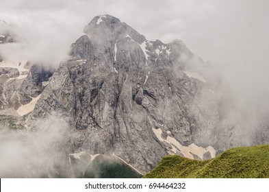 View of Gran Vernel summit, mountain of Marmolada massif, wrapped in clouds, as seen from Alta Via 2 trail #601 down to Fedaia lake from Viel del Pan refuge, Dolomites, Canazei, Trento, Italy