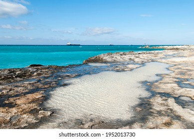 The view of Grand Bahama island rocky coastline with cargo ships in a background.