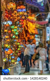 View of Grand Bazaar historical landmark of istanbul. Unknown saler works on colorful Turkish Ottoman lanterns and antique wall lamps while tourists and locals pass by.