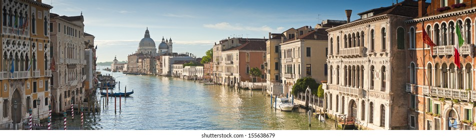 View of the Grand Canal and the stunning baroque Santa Maria Della Salute (1687) church in Venice and colourful villas bathed in early morning light. Stitched panoramic image.