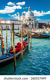View of Grand Canal in Venice, Italy, with colorful gondola boats in the foreground