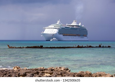 The view from Grand Cayman island Seven Mile Beach of a drifting cruise liner and the sunken ship remains (Cayman Islands).