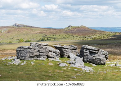 View of the granite bedrock outcrops at Top Tor, Dartmoor National Park, Devon,  on a bright cloudy day. To the east across the moorland in the background are Emsworthy Rocks and Saddle Tor.