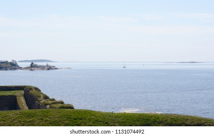 View from grassy hillside across Finnish waters from sea fortress Suomenlinna, Finland