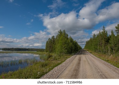 view of a gravel road along a lake in Lapland, Finland