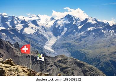 View of the great morteratsch glacier in engadin from piz languard. Swiss alpine landscape. Big mountains: Piz Bernina, Piz Palü. Swiss flag and  grisons flag