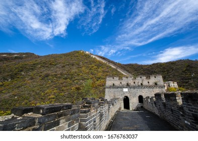 A view of the Great Wall of China trailing endlessly upward of the mountains.