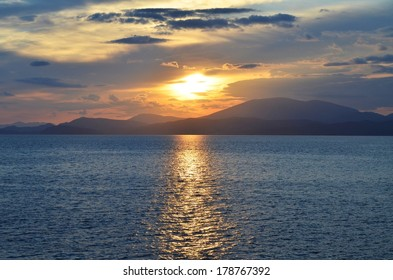 A view from the Greek island of Hydra, as the setting sun casts a channel of light across the sea.