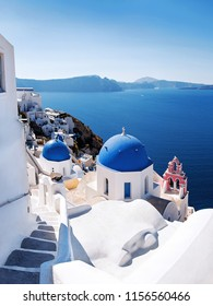 View with Greek orthodox church with blue domes and sea in Oia in Santorini, Greece, Europe. Beautiful scenery above the caldera overlooking the Aegean Sea.