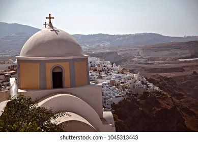 View of a Greek Orthodox church with white houses and hills in the background.
