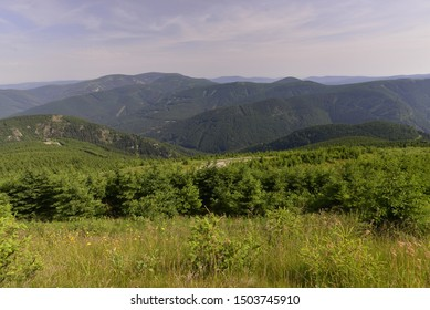 View of green hills under blue cloudy sky.