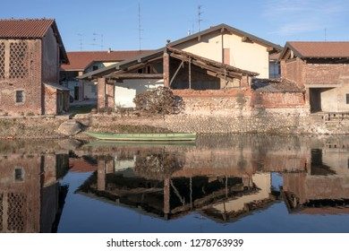 view of green old boat moored in front of traditional house on embankment of artificial historic canal, shot in winter bright light at Bernate Ticino, Milan, Lombardy, Italy