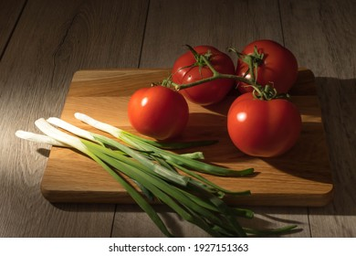 The view of green onion and bunch of tomatoes on the wooden cutting board. The dark photography of carving board with branch of tomatoes and spring onion on the wooden kitchen table.