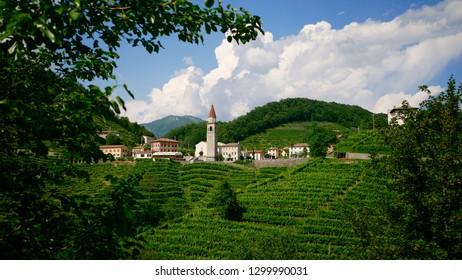 View of the green Prosecco wine hill and blue sky in background, Rolle, Cison di Valmarino, Strada del Prosecco, Chiesa dei Santi Giacomo e Filippo, Borgo tutelato dal FAI
